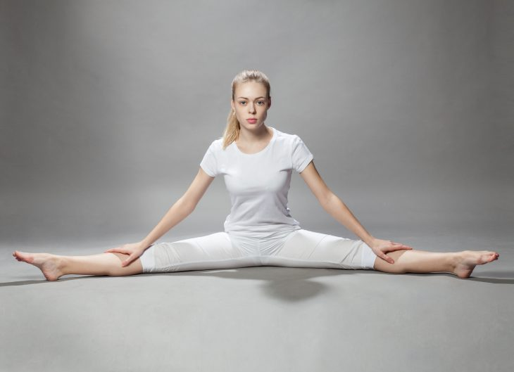 young beautiful woman makes exercises on gray background