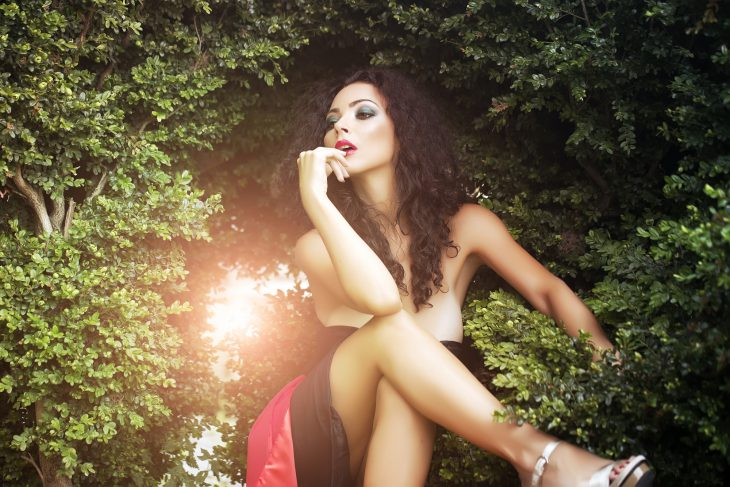 Glamour sexy woman posing near bush