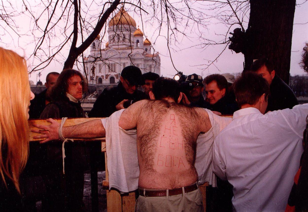 Олег Мавроматти распятый на кресте во время акции «Не верь глазам», 2000 год.