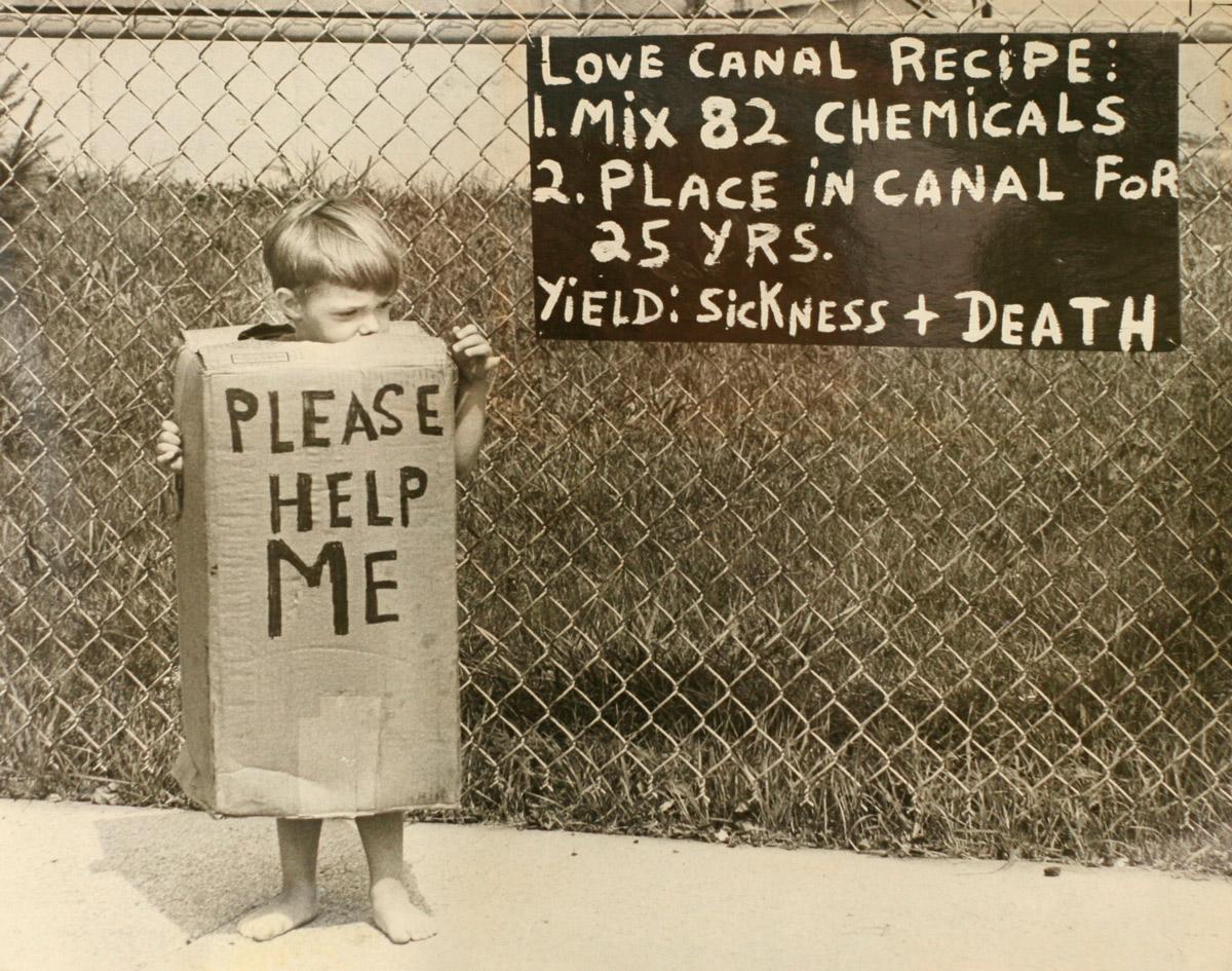 Ребенок в костюме из коробки с надписью «Пожалуйста, помогите мне» на фоне забора с табличкой «Рецепт Лав-Канала: Смешайте 82 химиката. Поместите в канал на 25 лет. Результат: болезнь + смерть»