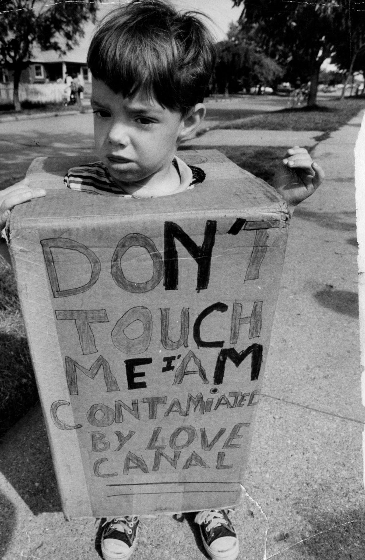 Ребенок в костюме из коробки с надписью «Не прикасайся ко мне, я загрязнен Лав-Каналом».