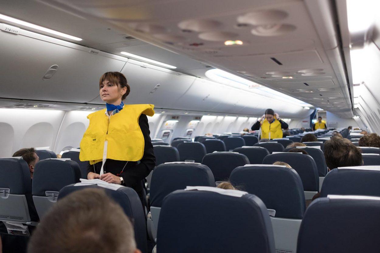 Стюардессы проводят инструктаж пассажиров перед полётом.