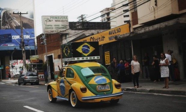 Brazilian attorney, Nelson Paviotti, drives one of his two Volkswagen Beetles painted with the colors of the national flag in Campinas