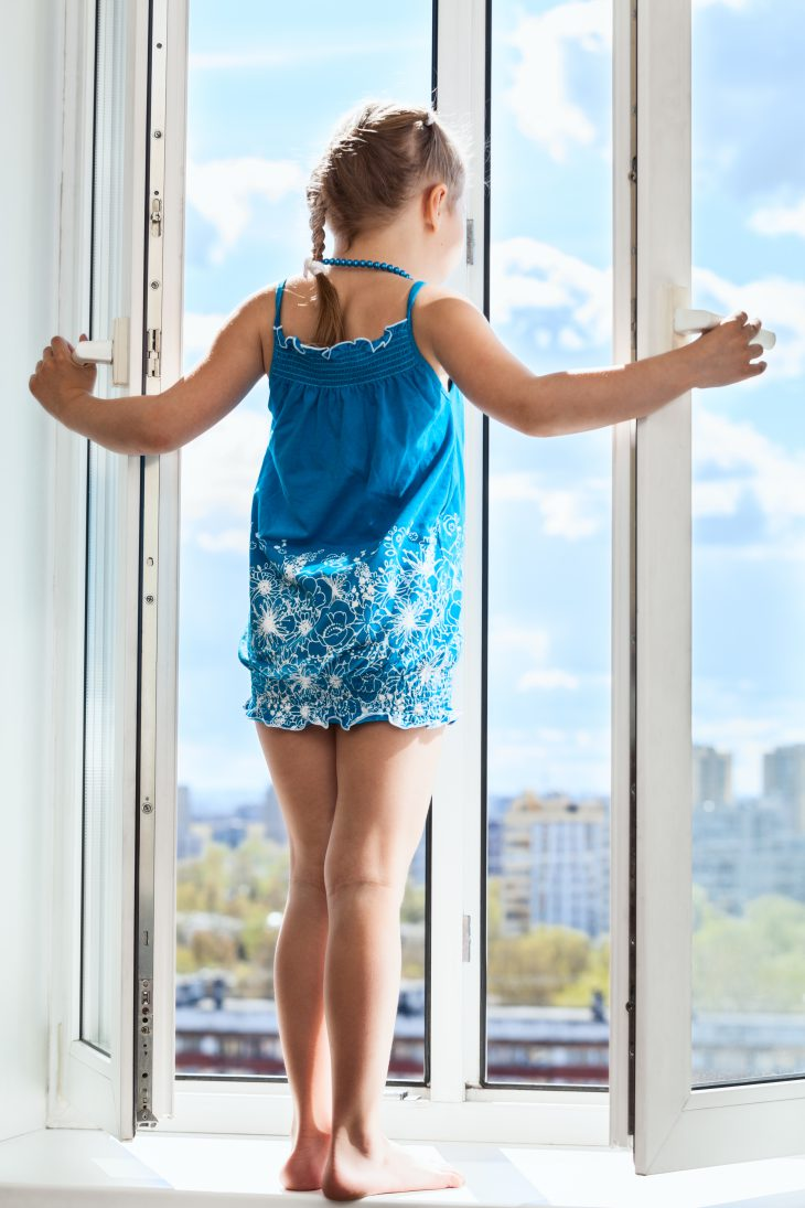 Young girl stand on window with opened door, looking from height